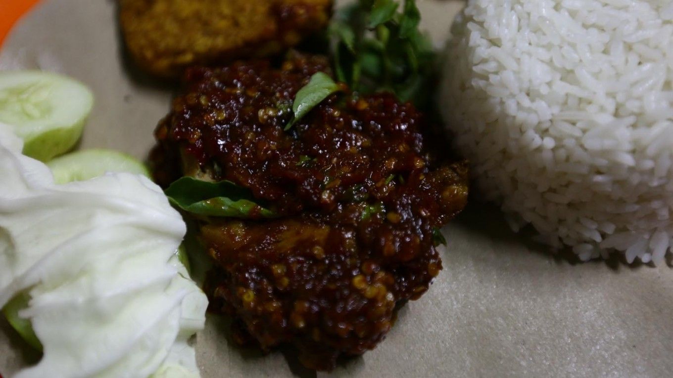 Covered in spices: 'Ayam penyet' (smashed fried chicken) Bu Sri, which is served with fried 'tempeh', raw vegetables and rice.