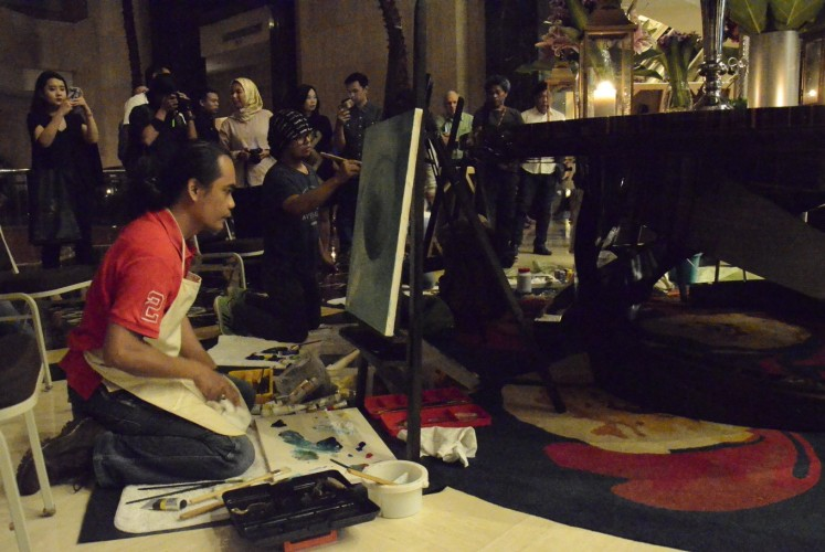 Indonesian artists Iwan Suhaya (left) and Kinkin (second left) paint in public during the Earth 'ART' Hour event at The Ritz-Carlton Jakarta in Mega Kuningan, South Jakarta, on Saturday.