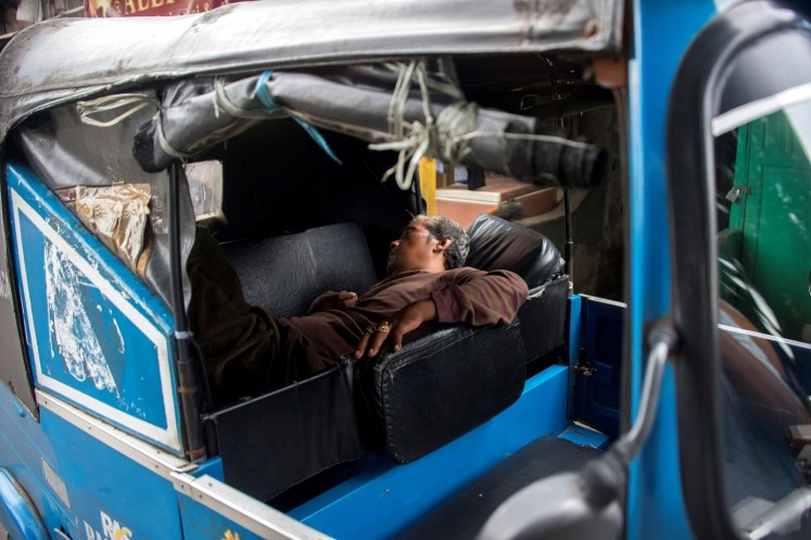 This photograph taken on February 13, 2018 shows a three-wheeled bajaj taxi driver taking a nap while waiting for passengers in Jakarta.