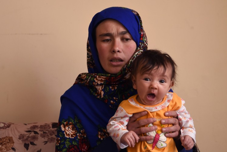 This picture taken on March 24, 2018 shows Afghan mother Jahantab Ahmadi, 25, holding her youngest child during an interview with AFP at a house in Kabul.
