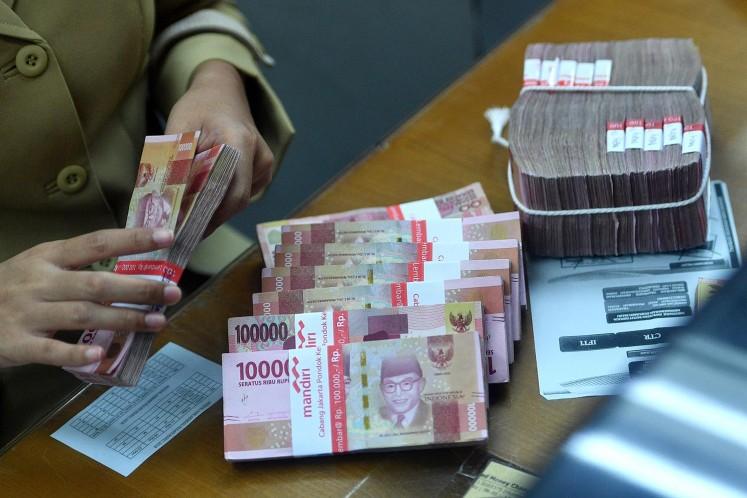 An employee counts rupiah bills at a money changer in Jakarta.