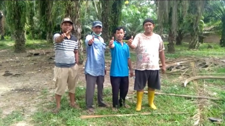 Tugimin (right) poses with his friends at his palm oil plantation in Simalungun regency, North Sumatra.