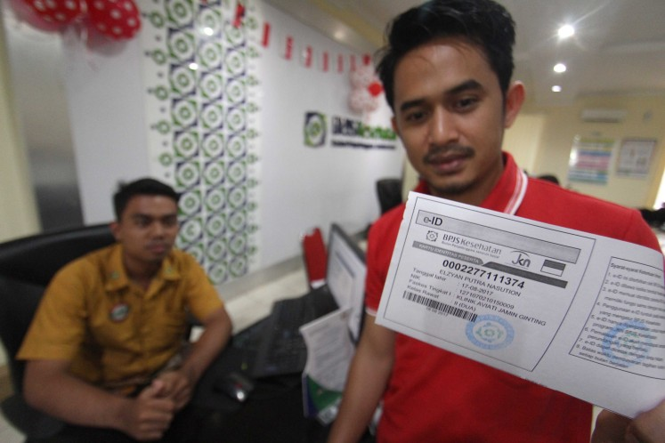 A father shows a copy of his infant son's universal health care card in this photo taken in August 2017.