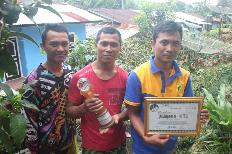Three siblings who fight for conservation (from left to right): Dasim, Kiryono and Jumpono, with their national champion trophy from the Indonesian specialty coffee competition.