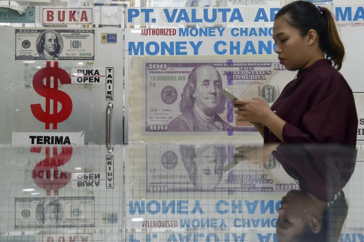 A woman waits in line at a money changer in Jakarta.