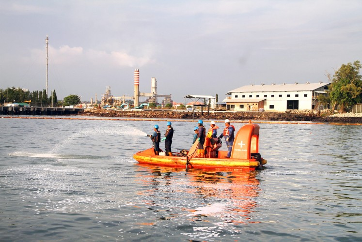 Cleaning up the mess: Officials from state-owned oil and gas company Pertamina spray dispersant fluid to clear an oil spill in Balikpapan Bay, East Kalimantan, last week. The oil reportedly leaked from a broken pipe belonging to Pertamina.