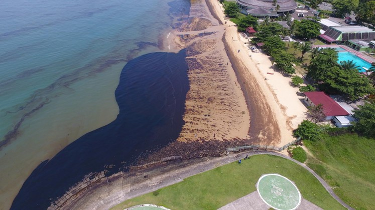 This aerial picture taken on April 2, 2018 shows some of the oil spill on Benua Patra beach in Balikpapan. An oil spill off Borneo island that led to five deaths and the declaration of a state of emergency was caused by a ruptured undersea pipe, Indonesia's national oil company Pertamina said on April 4.