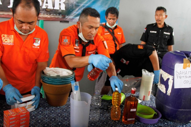 Sampling: Crime scene investigators from the Bandung Police check bottles found on Thursday in a house suspected to be a production site of bootleg liquor in Bandung regency of West Java.