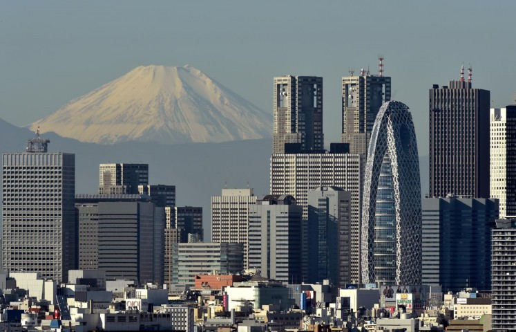 Japan's highest mountain, Mount Fuji at 3,776m, is seen behind skyscrapers in Tokyo's Shinjuku area on November 28, 2015.