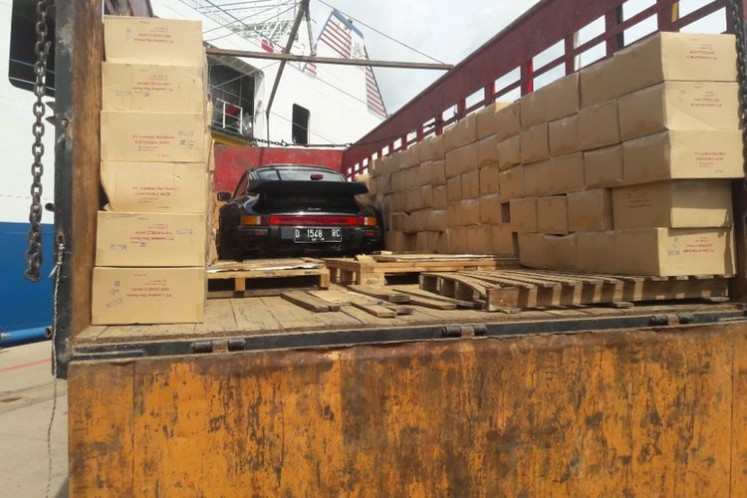 A Porsche Turbo S is hidden on a truck on board of the Fajar Bahari V vessel and is covered with cardboards.