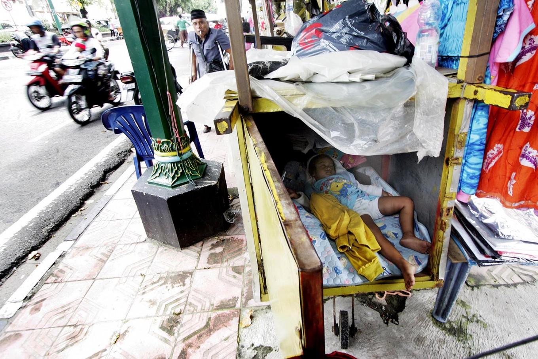 A trader's child sleeps on the sidewalk. JP/Boy T. Harjanto