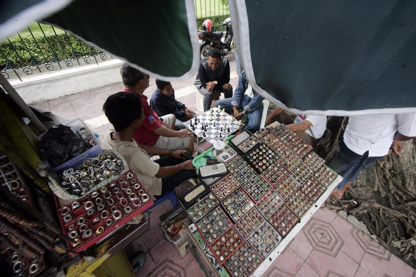 Traders play chess to pass the time while waiting for customers. JP/Boy T. Harjanto