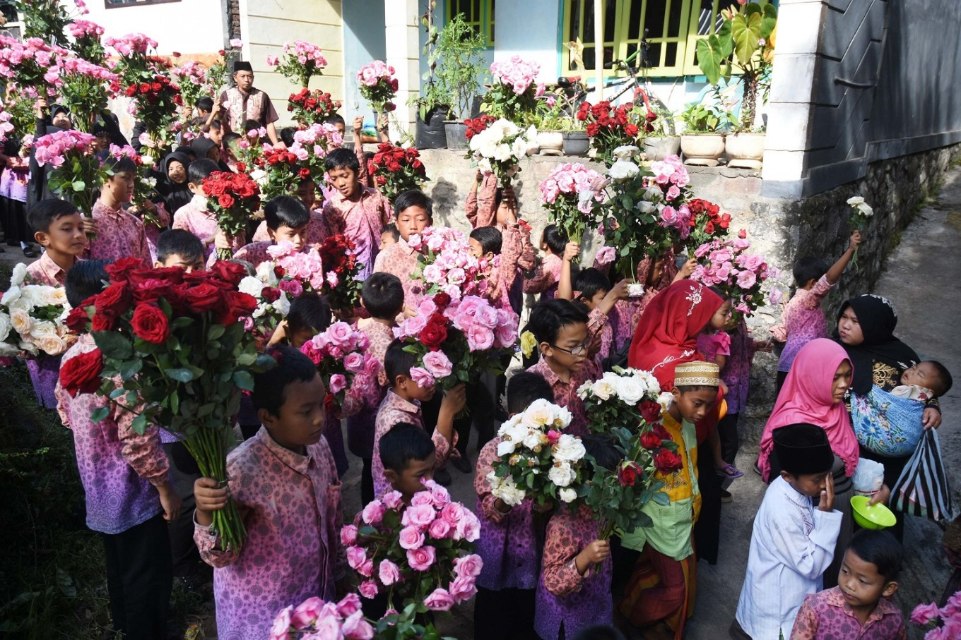 Friends with roses in hand accompany children to be circumcised in Blumbang Macari lake.