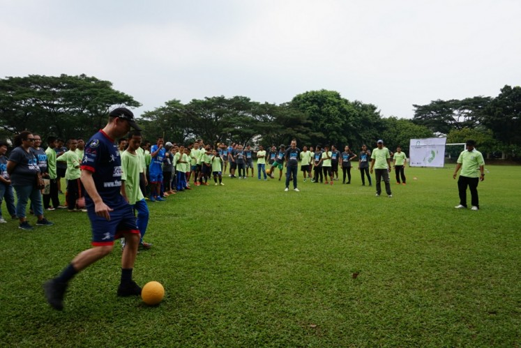 Lee Hawkins (left), technical manager of ASA Foundation, kicks a ball to commence StarCoach, a project between Starbucks and ASA Foundation, on April 15, at Global Jaya School in South Tangerang, Banten.