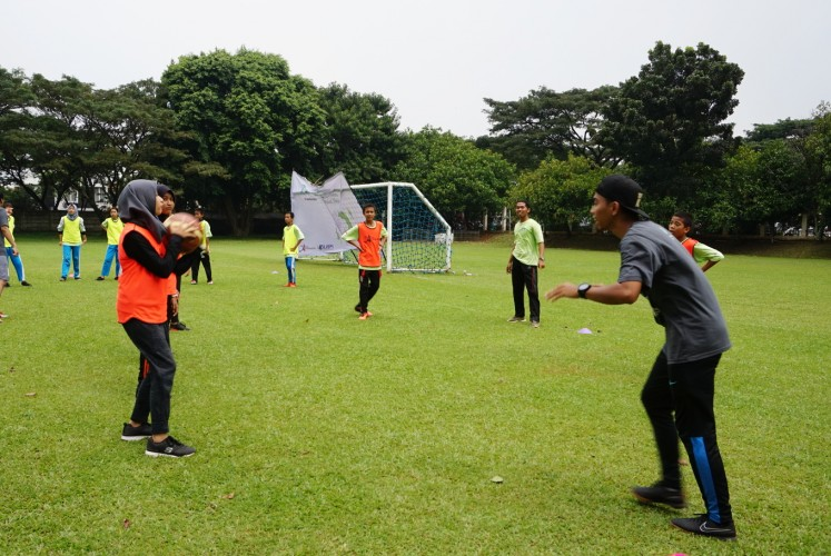 A student learns to pass a ball with a Starbucks employee for  the StarCoach project at Global Jaya School in South Tangerang, Banten, on, April 15.