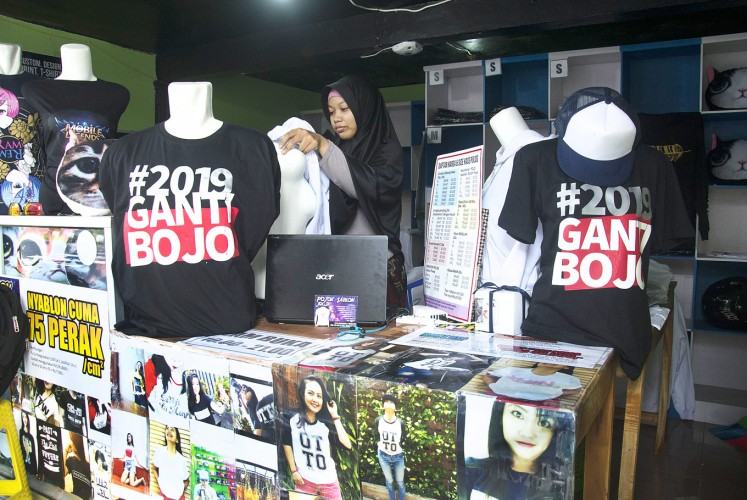A staff member of a t-shirt shop in Yogyakarta's Umbulharjo district, where a number of tourist sites are located, waits for customers to buy t-shirts displaying the pun #2019GantiBojo (2019 change your spouse). The t-shirt slogan is a play on #2019GantiPresiden (2019 change the President), which has gone viral on social media ahead of the 2019 presidential election. The T-shirts are sold for Rp 125,000 (US$9.08).