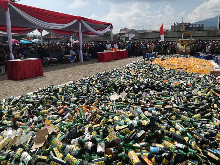 Dangerous substance: Thousands of bottles of 'oplosan' (bootleg liquor) are destroyed at Alun-Alun Cicalengka, Bandung regency, West Java, on April 19.