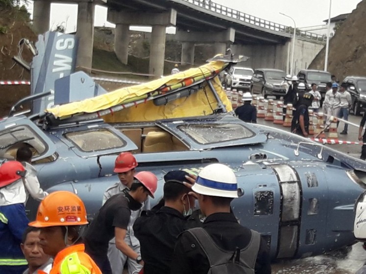 First responders: Officials respond to a helicopter crash inside an industrial park in Morowali, Central Sulawesi, on Friday. The helicopter was carrying six Chinese nationals.