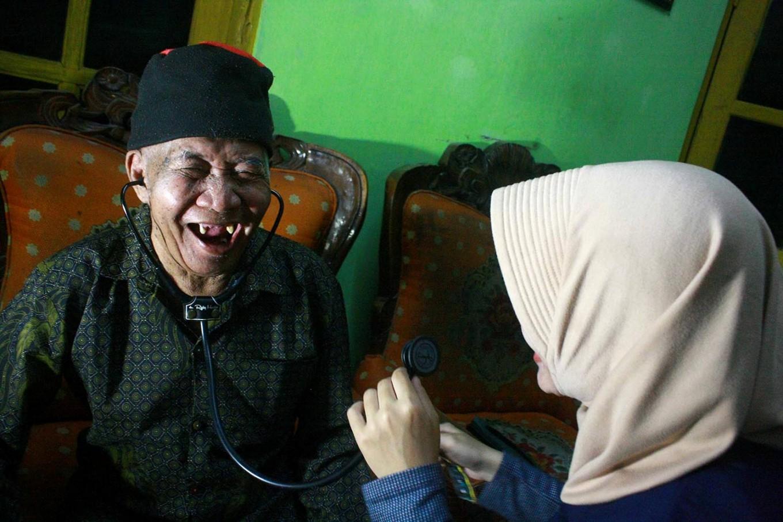 An elderly man smiles while receiving treatment. JP/Maksum Nur Fauzan