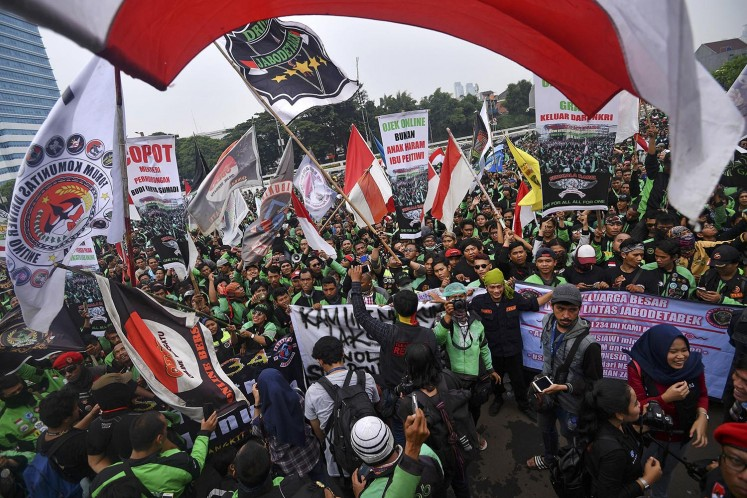 Thousands of online 'ojek' (motorcycle taxi) drivers rally in front of the House of Representatives building in April last year. They demanded that the government regulate tariffs.