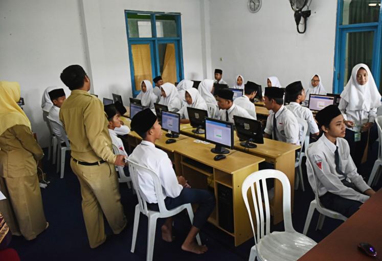 Get ready: Teachers give instructions to students of  Madrasah Tsanawiyah Hidayatul Mubtadiin junior high school in Malang, East Java, before they start the computer-based national exams on April 23.