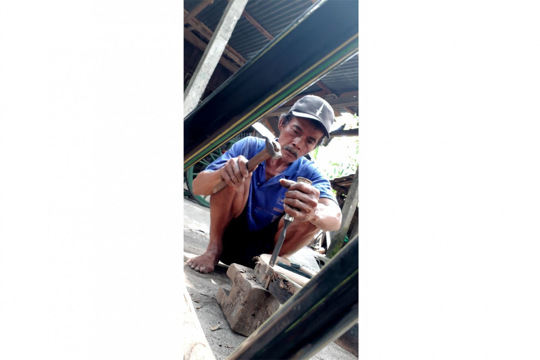 Delicate work: A repairman carefully chisels a wooden wheel. JP/R. Berto Wedhatama