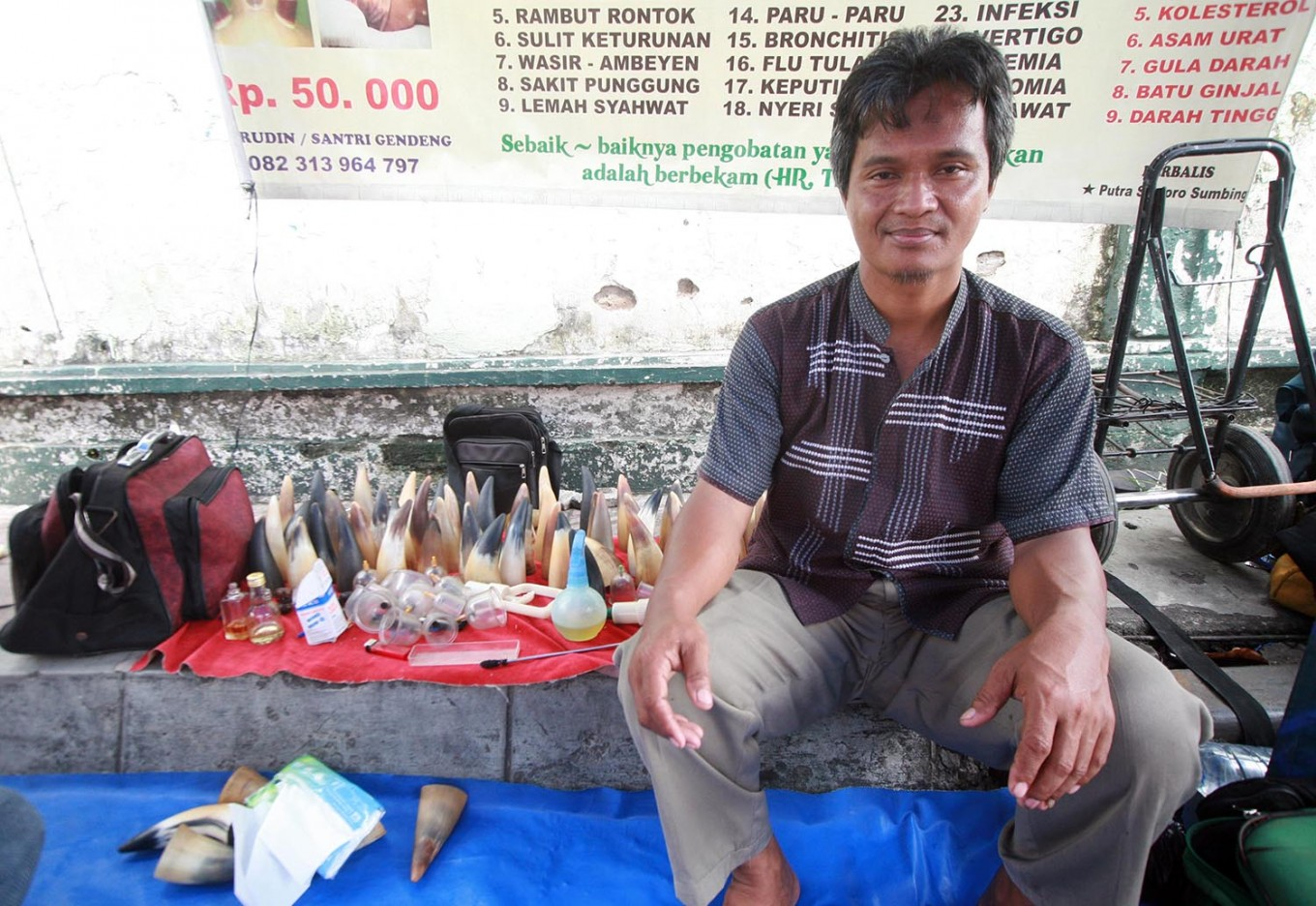 Amirudin sits in his makeshift tent at the market. He has practiced cupping therapy since he was 17 years old. JP/Boy T. Harjanto