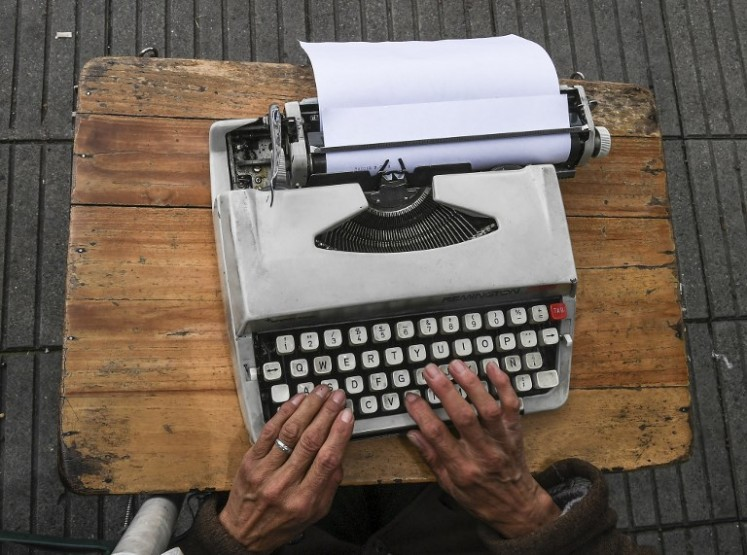 Street clerk Candelaria Pinilla,63, types a letter on her typewriter, in front of the district taxing office in Bogota, on April 9, 2018 Street clerks are experts in filling out forms, documents and even in typing letters, to help their clients with paperwork.