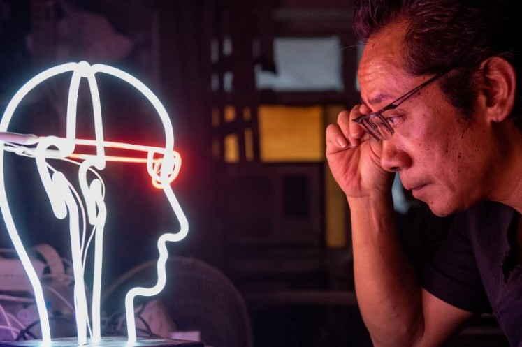In this picture taken on April 16, 2018, neon sign maker Wu Chi-kai looks at one of his works.