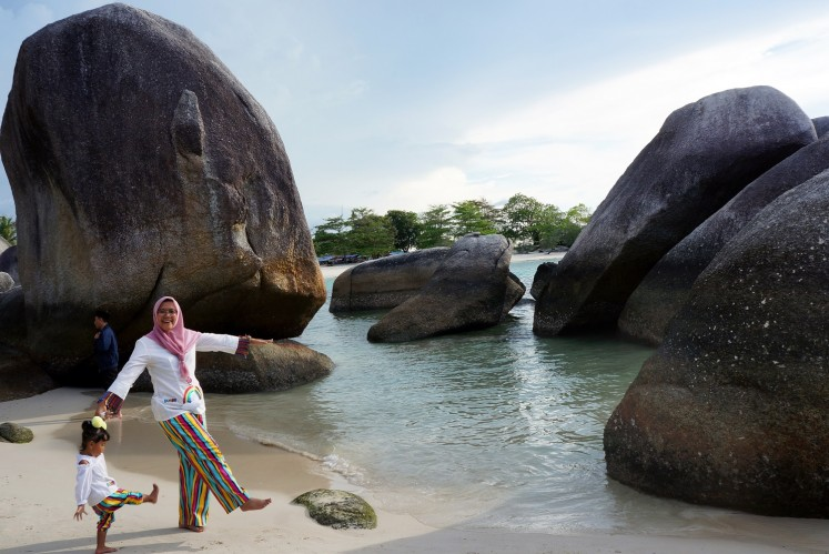 Visitors pose for a photograph while strolling along Tanjong Tinggi Beach on Belitung Island in Bangka-Belitung Islands province. This beach was one of the shooting locations for Laskar Pelangi.
