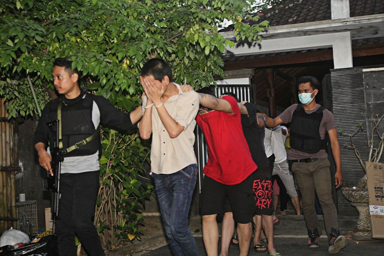 Suspected: Bali Police personnel escort Chinese nationals arrested on Tuesday over alleged cybercrimes.