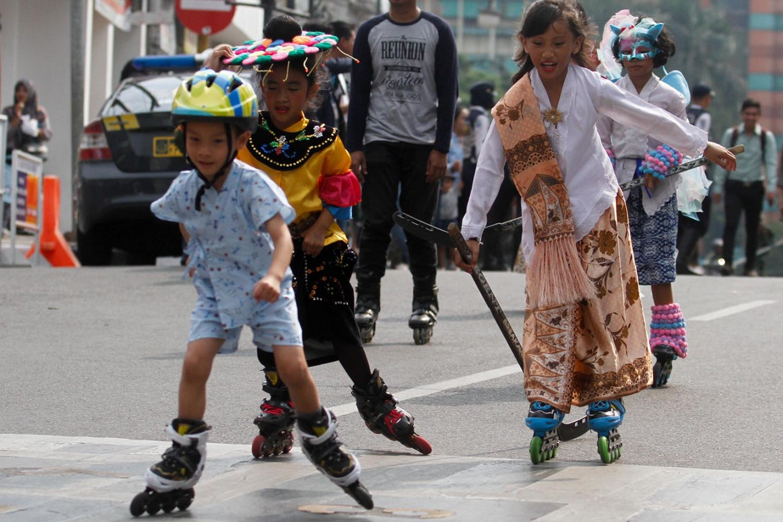 Children roller skate in traditional costumes during the carnival. JP/Arya Dipa