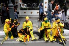 Exhausted performers from Lamandau regency, Central Kalimantan, take a rest on the sidewalk. JP/Arya Dipa