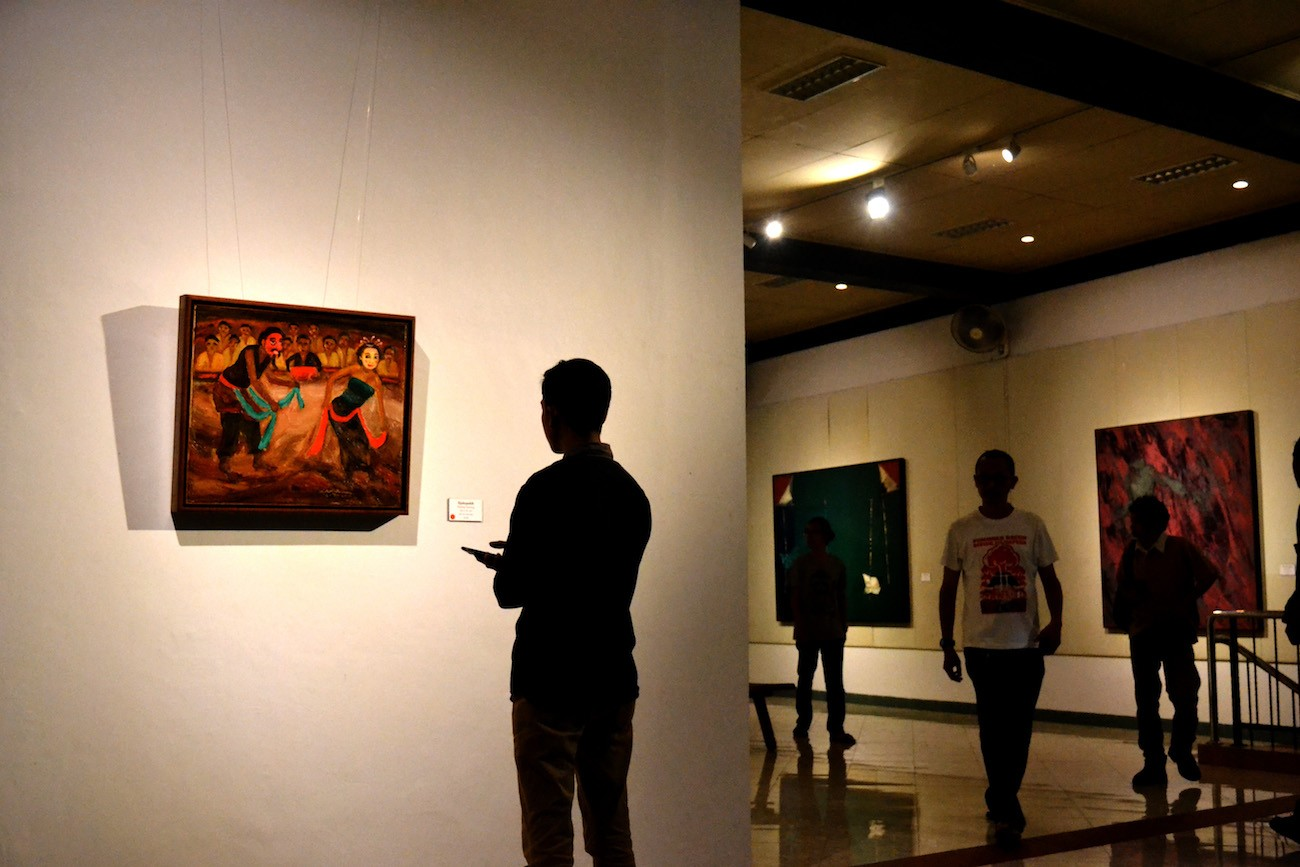 Visitors observe paintings displayed at the Seninjong exhibition.