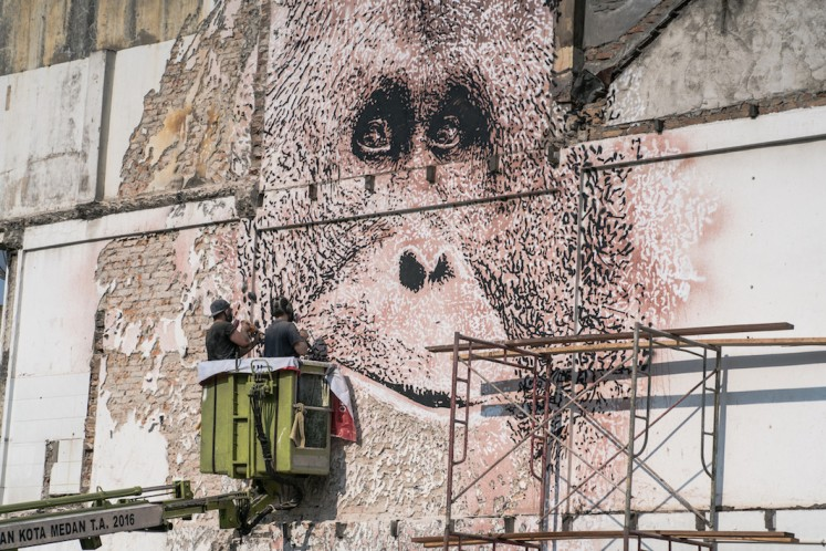 Portuguese street artist Vhils chisels an orangutan's face on the side of a building at the Majestik traffic circle area in Medan in March. (Courtesy of Sumatran Orangutan Society/Skaiste)