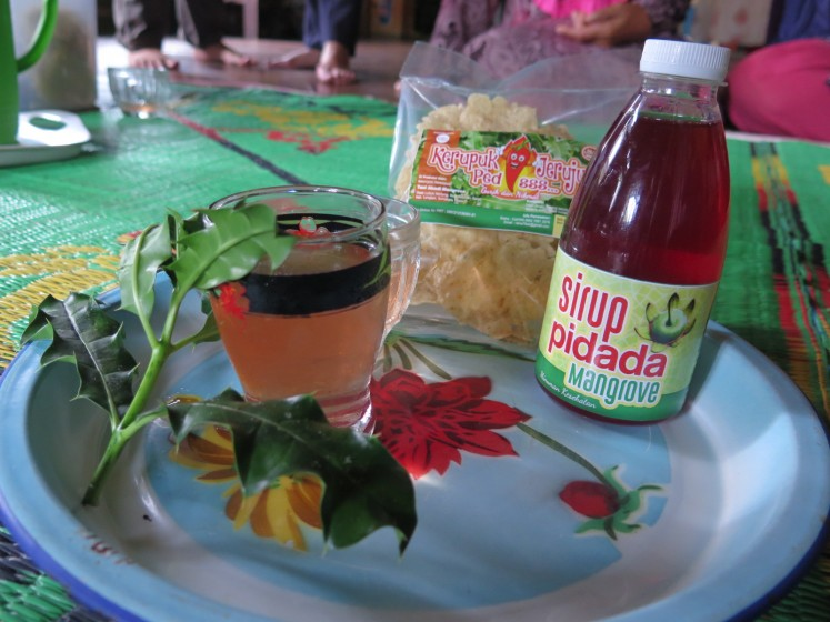 A pack of kerupuk jeruju, a snack made from acanthus leaves, and a bottle of pidada, a syrup made from mangrove apples, are arranged on a plate. After the HKm permit issue in 2017, some 14 Lubuk Kertang women established their own group named Kelompok Tani Abadi Mangrove to produce kerupuk jeruju and pidada syrup. (JP/Moses Ompusunggu)