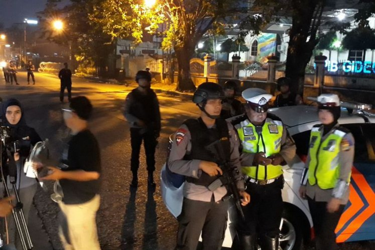 Police officers cordon off a road in front of the Police Mobile Brigade headquarters (Mako Brimob) in Depok, West Java, on Wednesday morning following a riot inside the Mako Brimob detention center.