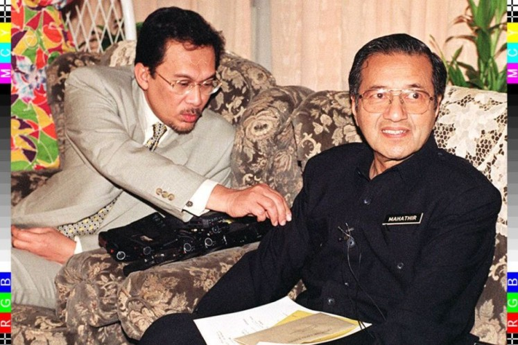 Anwar Ibrahim removes a ball of dust from  Mahathir's sleeve during a press conference in 1997.