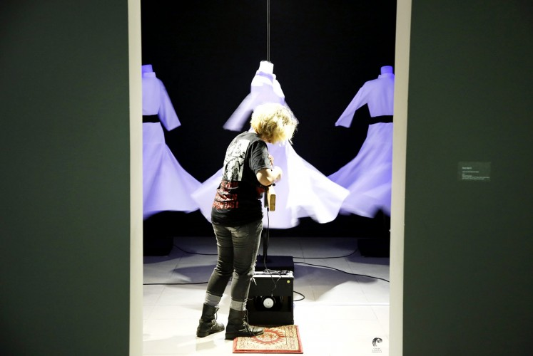 War on war: An installation transforms an AK-47 assault rifle into a guitar, aiming it at Middle Eastern-inspired garb.
