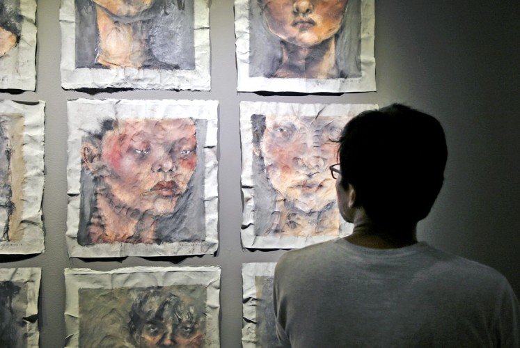 Admiration: A visitor admires an abstract painting of significant depth.