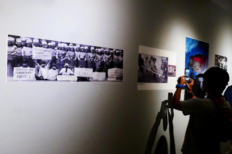 Visitors look at photos from Indonesia's reformation period.