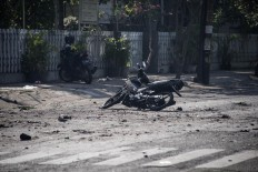 A damaged motorbike is seen at the scene outside a church following a suicide bomb in Surabaya on May 13, 2018. At least two people were killed and 13 others injured in bomb attacks, including a suicide blast, targeting churches in Indonesia's second biggest city Surabaya, police said. AFP/ Juni Kriswanto