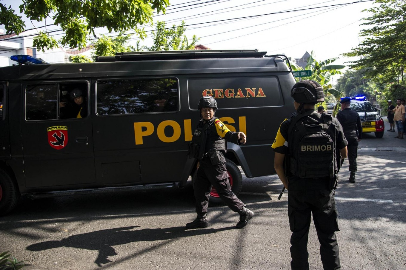Indonesian policemen patrol outside a church following a suicide bomb in Surabaya on May 13, 2018. At least two people were killed and 13 others injured in bomb attacks, including a suicide blast, targeting churches in Indonesia's second biggest city Surabaya, police said. AFP/ Juni Kriswanto