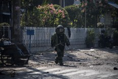 An Indonesian bomb squad member examines the site following a suicide bomb outside a church in Surabaya on May 13, 2018. At least two people were killed and 13 others injured in bomb attacks, including a suicide blast, targeting churches in Indonesia's second biggest city Surabaya, police said. AFP/ Juni Kriswanto