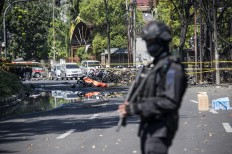 An Indonesian anti-terror policeman stands guard at the blast site following a suicide bomb outside a church in Surabaya on May 13, 2018. A wave of blasts including a suicide bombing struck outside churches in Indonesia, killing at least six and wounding dozens of others, police said, the latest assault on a religious minority in the world's biggest Muslim-majority country. AFP/ Juni Kriswanto