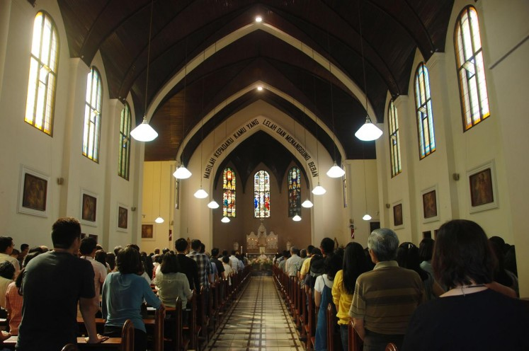 Congregants attend a Sunday service, as police stand guard outside, in Saint Peter's Church in Bandung, West Java, on Sunday. A wave of blasts including a suicide bombing struck churches in Surabaya, East Java, on Sunday, killing at least 10 and wounding dozens of others, police have said.