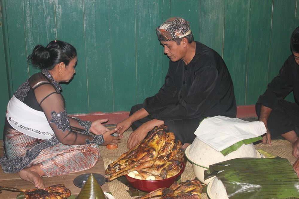 Emik hands the offering over to Ukat, her husband.