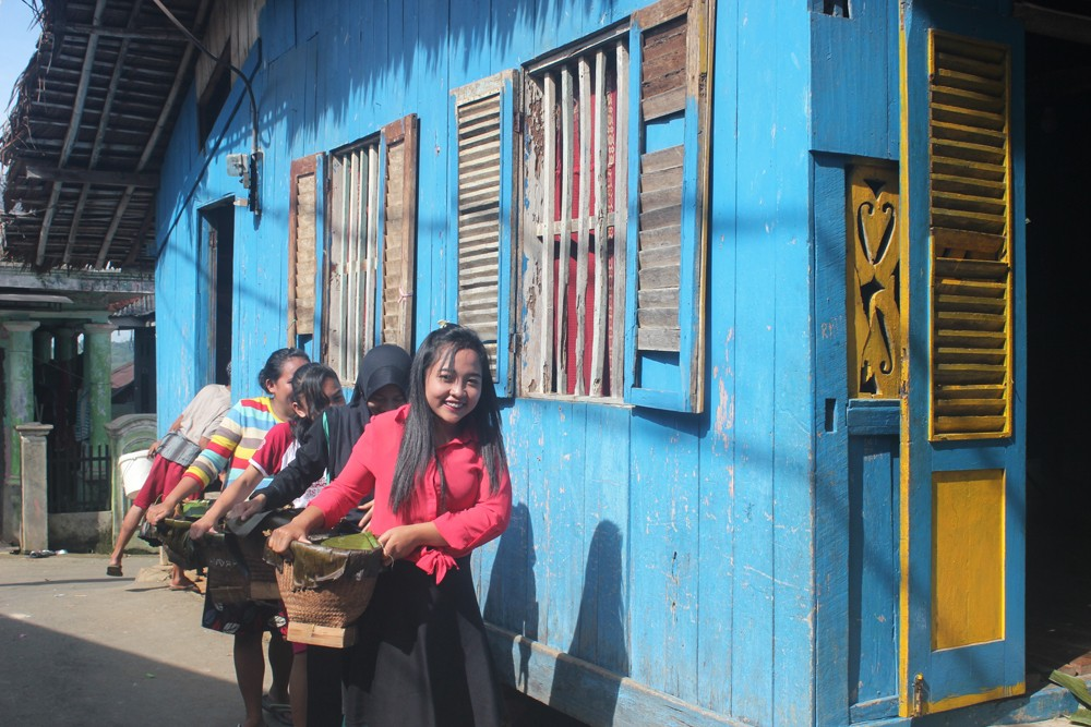Women in the traditional Sundanese community of Sukardi carry baskets of rice as offerings.