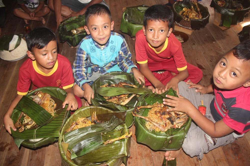 Children receive baskets of rice to eat together.