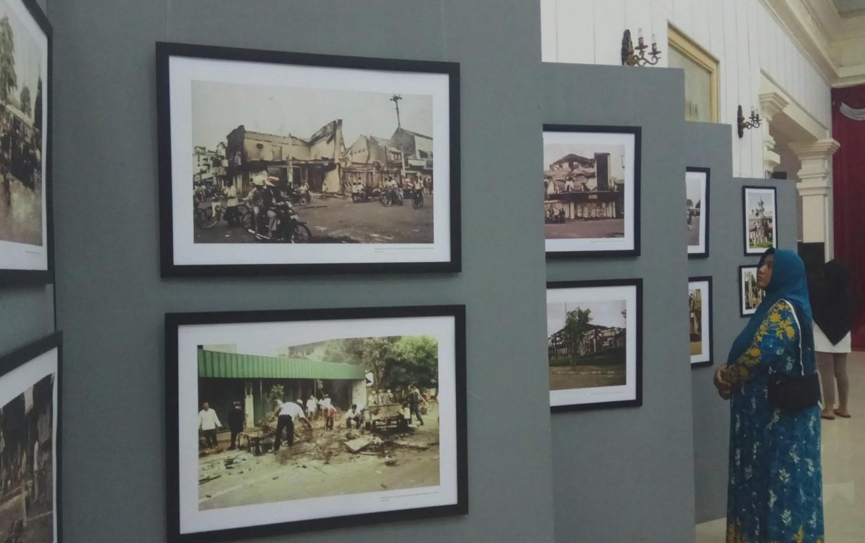 Visitors look at exhibition photos.